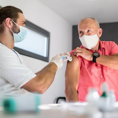 Älterer Mann erhält Impfung