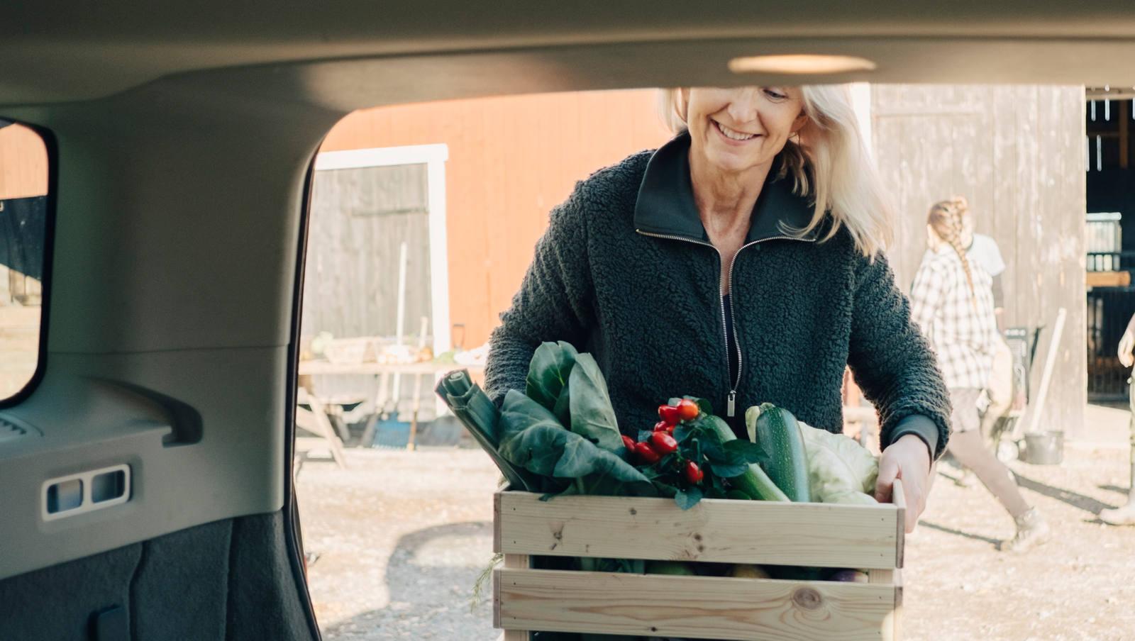 Frau trägt eine Holzkiste mit Marktgemüse zum Auto.