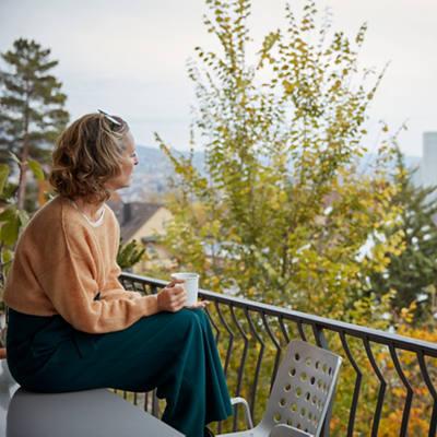 Frau relaxt auf ihrem Balkon
