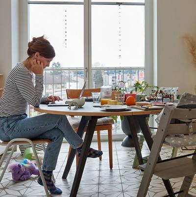 Frau sitzt mit Laptop am Esstisch