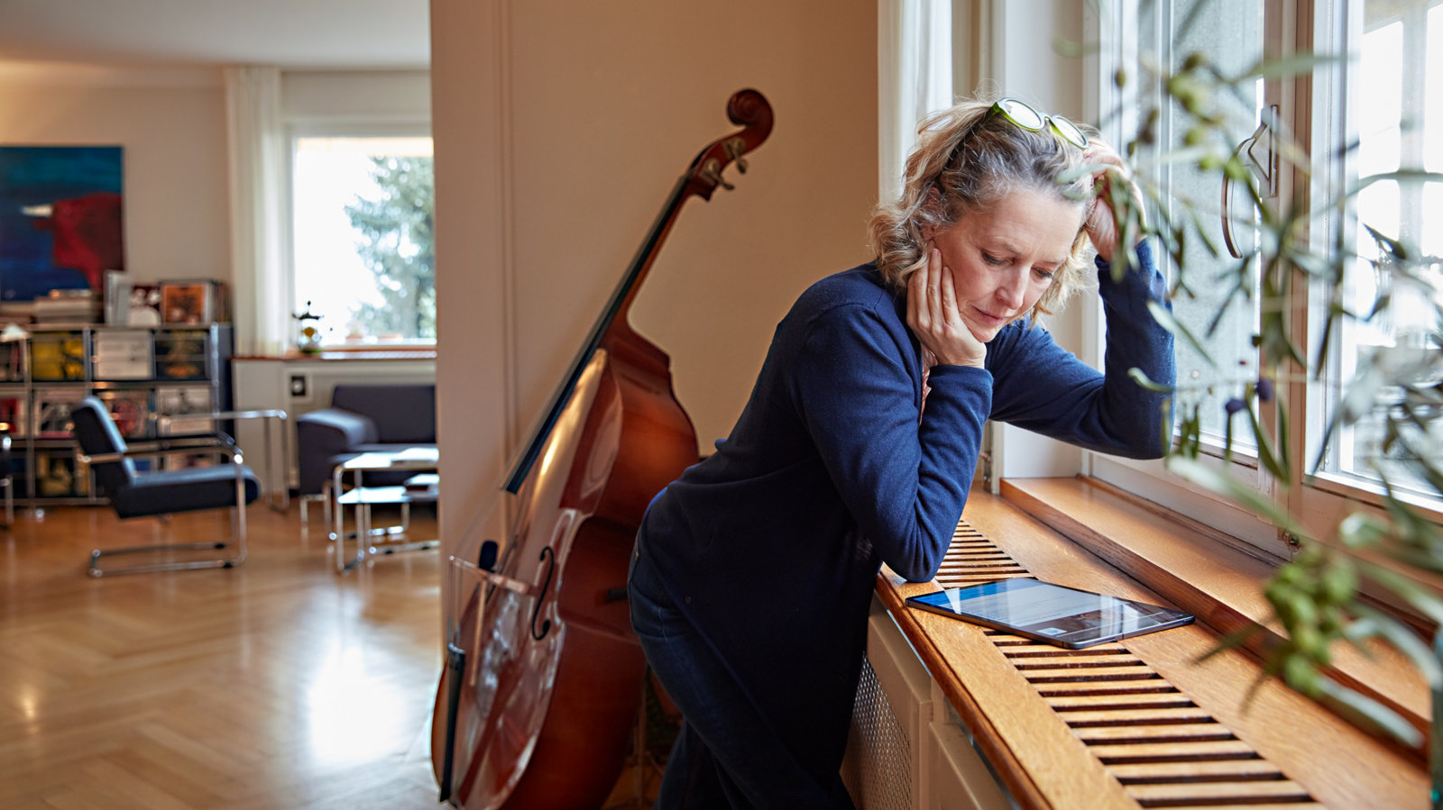 Frau studiert Tablet vor ihrem Cello am Fenster