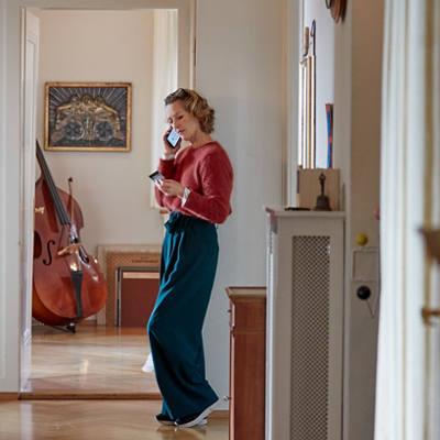 Frau am Telefon vor ihrem Cello