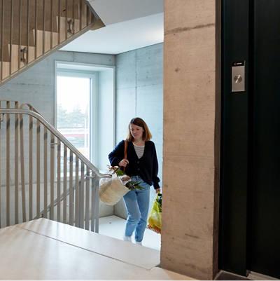 Frau mit Einkäufen im Treppenhaus