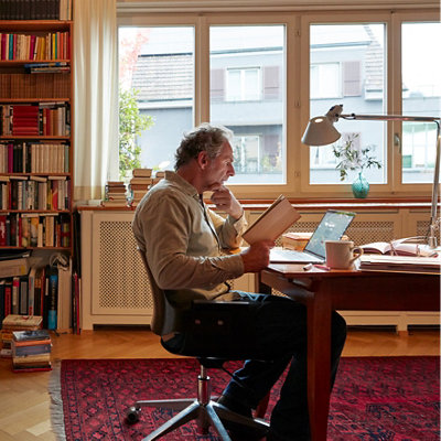 Mann im Büro vor Bibliothek
