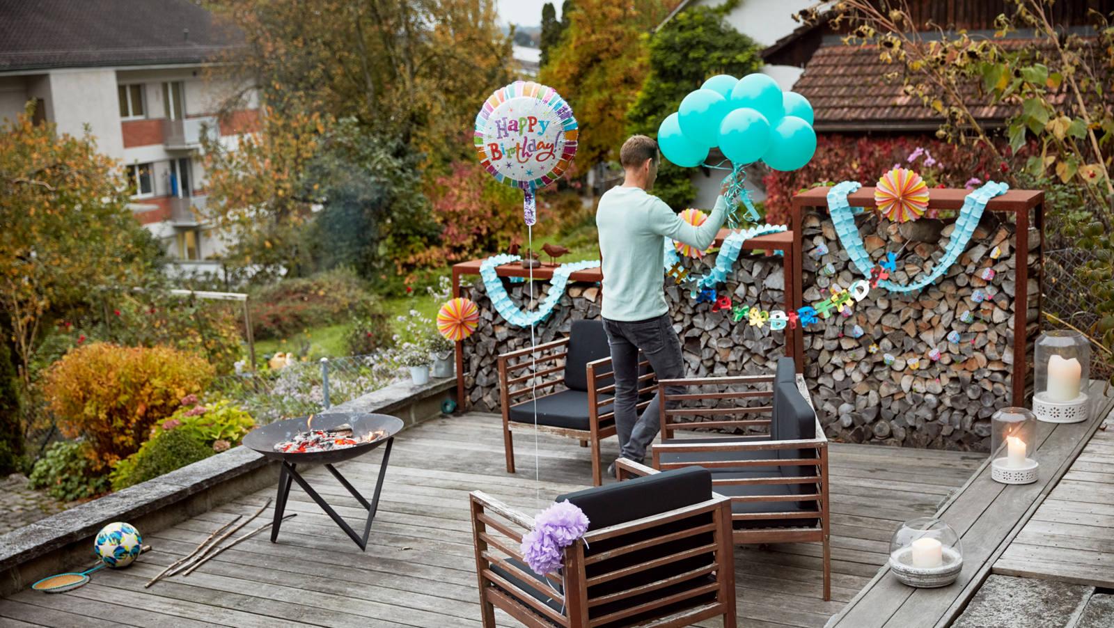Mann dekoriert Terrasse für eine Geburtstag-Party
