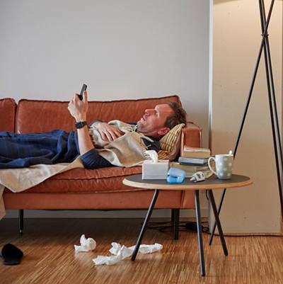 Mann liegt krank auf dem Sofa