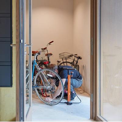 Mann pumpt Fahrraddreifen im Eingang eines Mehrfamilienhauses