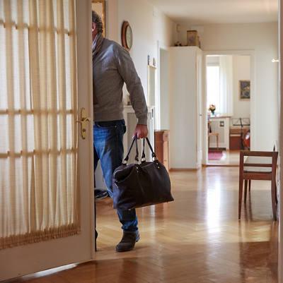 Mann verlässt mit Reisetasche Wohnung