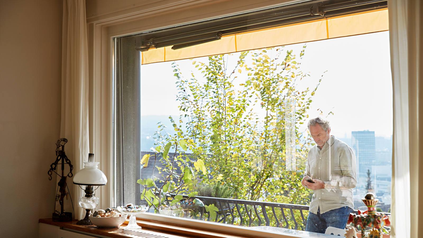 Mann mit Smartphone auf dem Balkon