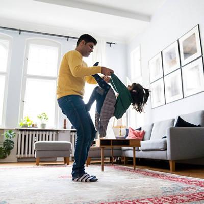 Vater spielt mit Tochter im Wohnzimmer