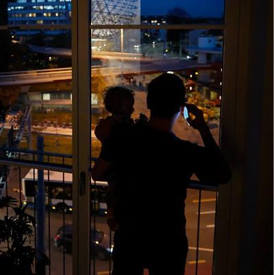 Vater telefoniert mit Kind auf dem Arm in der Nacht