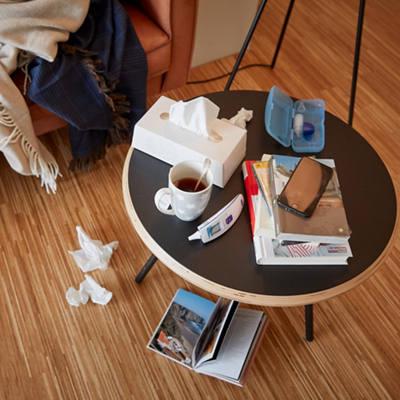 Tisch mit Erklältungsutensilien wie Fiebermesser, Tee und Kleenex-Box
