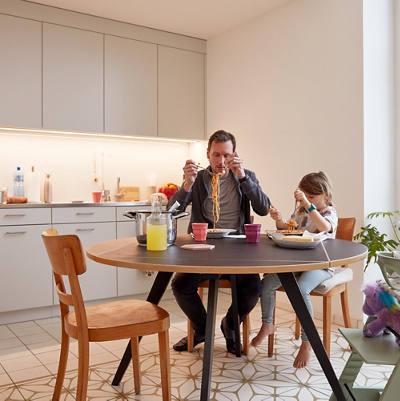 Vater und Tochter essen Spaghetti am Küchentisch