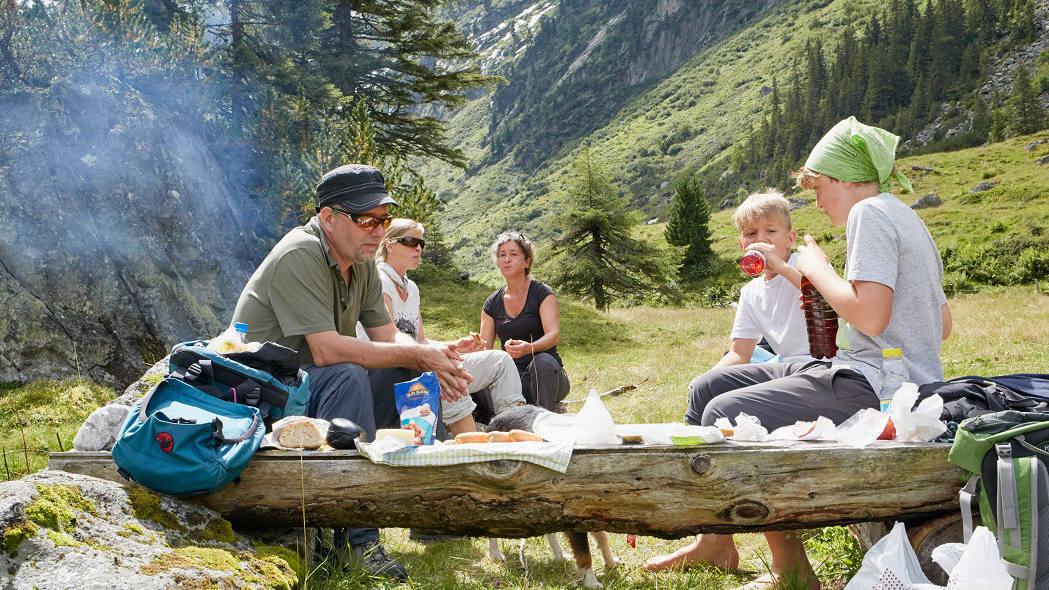 Beim Wandern geniesst eine Familie ihre Picknick-Pause