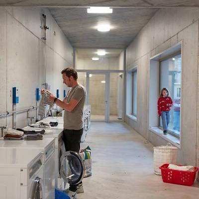 Mann wäscht Wäsche in einer Waschküche